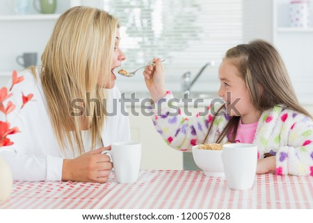 Girl feeding her mother at the kitchen - stock photo