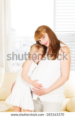 Girl feeling her mother's pregnant belly. - stock photo