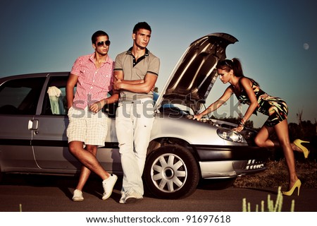 girl fixing car engine while couple of young man waiting by the car - stock photo
