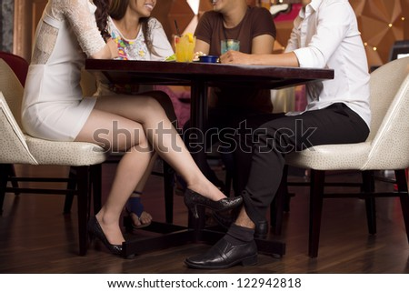 Girl flirting with a guy in a cafe while having fun with the friends - stock photo