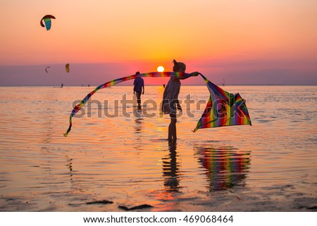 girl flying a kite on the sea in sunset time