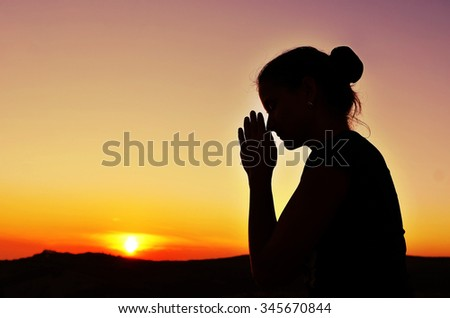 Girl folded her hands in prayer. Beautiful sunset. Colorful sky. Tenderness and serenity - stock photo