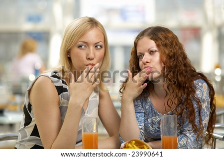 Girl-friends eat snack in cafe and lick fingers