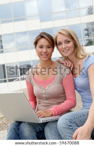 Girl friends in college campus with laptop computer