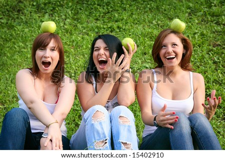 Girl friends with apples in the park - stock photo