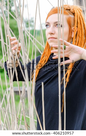 Girl from a fairy tale goes by and tries to cross the reed or bamboo sticks