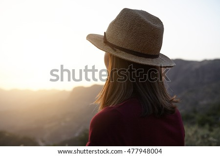 Girl from behind looking at something over the mountains in very bright sun in front of her wearing a t-shirts at sunset
