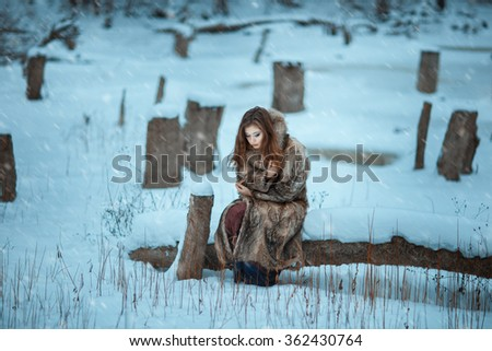 Girl froze in the winter woods. Around covered with snow and it is cold. - stock photo
