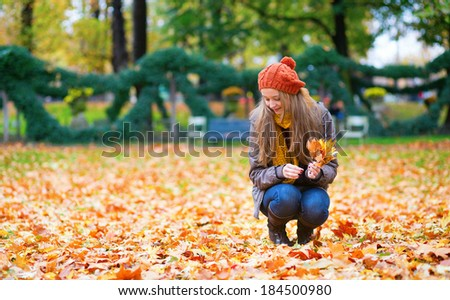 Girl gathering autumn leaves in park.