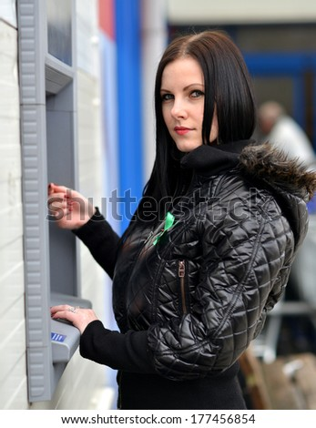 Girl get cash from an ATM on a city street - stock photo