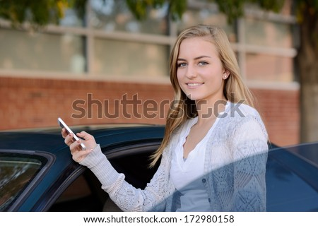 Girl getting in the car. Young woman holding a smartphone while entering a car.