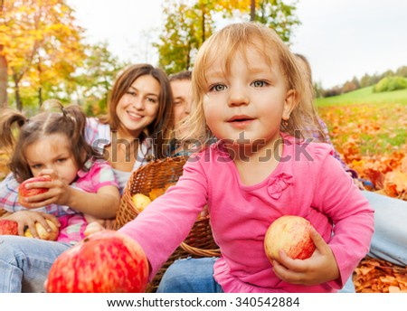 Girl gives apples with happy family sit behind - stock photo