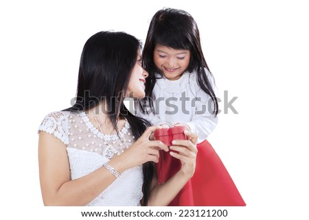 Girl giving a gift box to her mother in studio, isolated over white background - stock photo