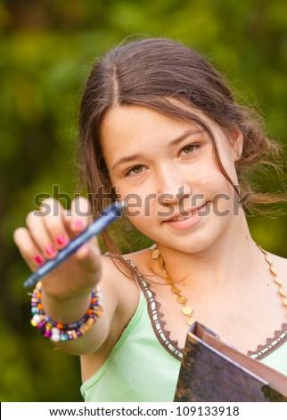 Girl giving a pen, portrait - stock photo