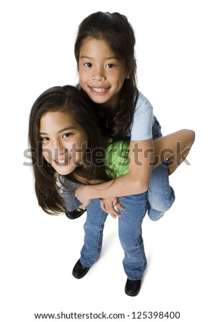 Girl giving piggy back ride to her sister