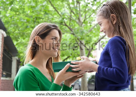 Girl giving to her mother a christmas present