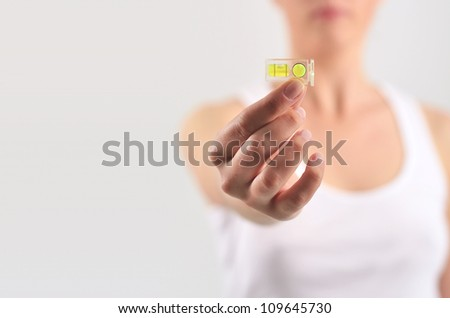 Girl giving to someone a spirit level - stock photo