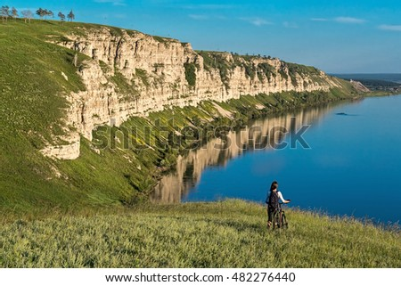 girl goes with bike on the hill in the river background, Siberia