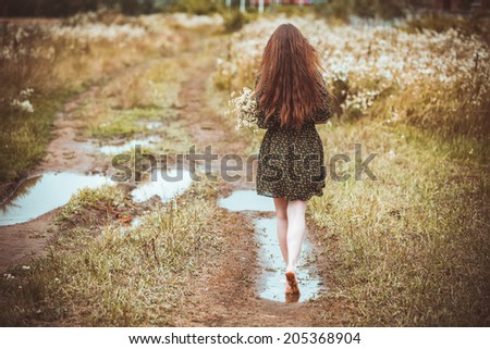 girl going on rural road with a bouquet of wild flowers - stock photo