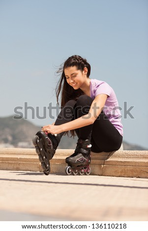 Girl going rollerblading sitting putting on in line skates outdoors - stock photo