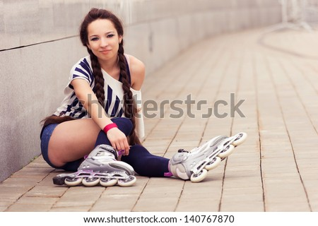 girl going rollerblading sitting putting on inline skates - stock photo
