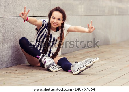 girl going rollerblading sitting putting on inline skates. outdoors portrait - stock photo
