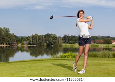 Girl golf player teeing-off with driver from tee-box, front view. - stock photo