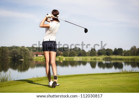 Girl golf player with driver teeing-off from tee-box to shoot over lake, view from behind.