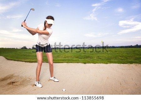 Girl golfer preparing for chipping the ball out of the sand trap. - stock photo