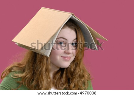 Girl goofing around with book on her head instead of studying - stock photo