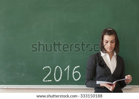 Girl graduate student on a green blackboard, chalk drawn date in 2016, a difficult choice future profession to graduates - stock photo