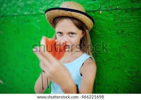 girl greedily eating ripe watermelon on a green background