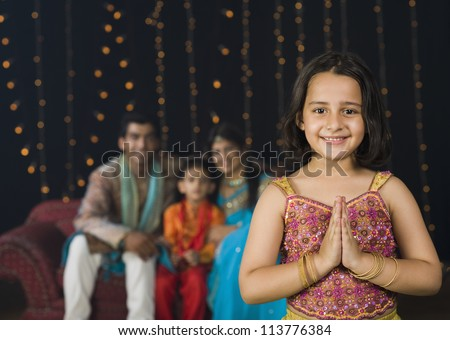 Girl greeting on Diwali festival with her family in the background - stock photo