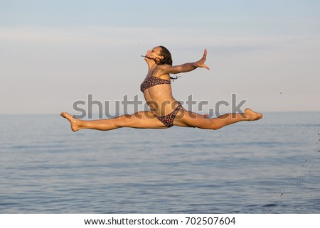 Girl gymnast flies over the water in the sea