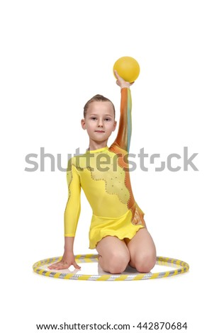 girl gymnast in yellow clothes posing with hula hoop and ball - stock photo