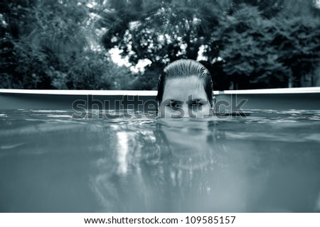 Girl half face in the water looking directly at the camera