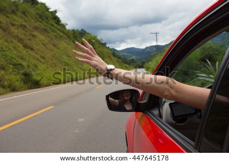 girl hand at the car window on an empty country road - stock photo