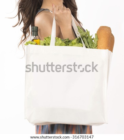 girl hand hold white clean bag full with vegetables and olive wine