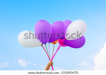 Girl hand holding colorful balloons to the sky