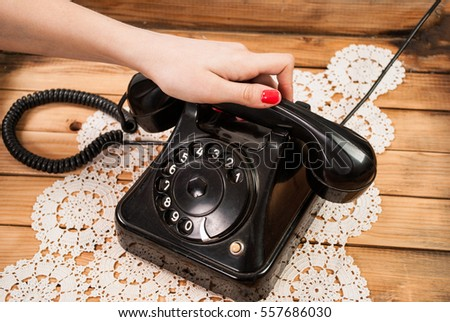 Girl hand holding old telephone headset on lace tablecloths and wooden background