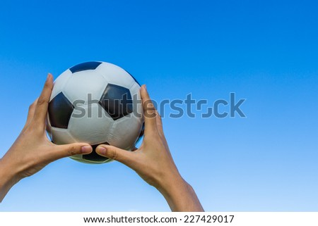 Girl hand holds a soccer ball in the sky on blue sky background.