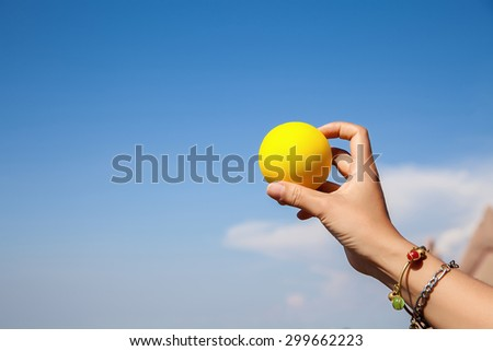Girl hand holds a yellow ball in the sky background.
