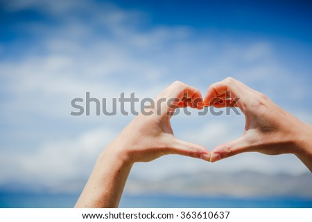 Girl hand in heart form love blue sky