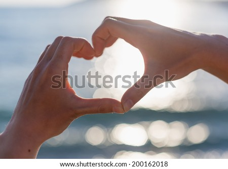Girl hand in heart form love with ocean sunset background  - stock photo
