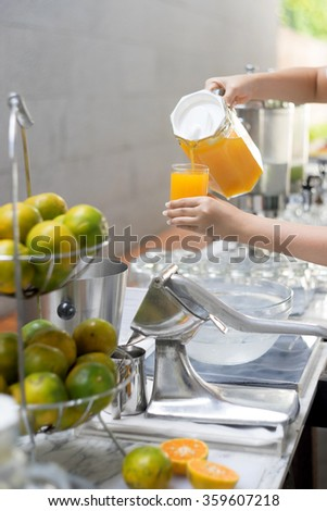 Girl hand pouring orange juice into glass
