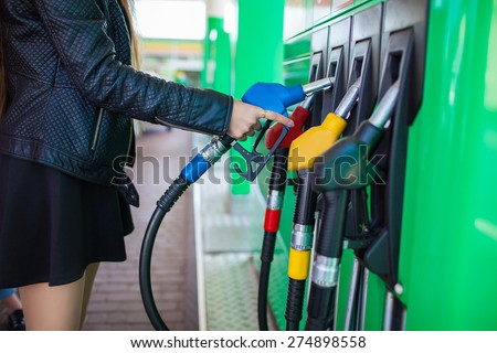 Girl hand with fuel pump at a gas station - stock photo