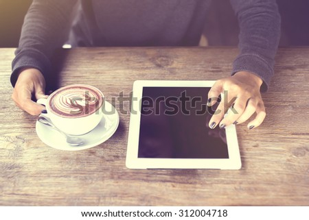 Girl hands, digital tablet and coffee, vintage photo effect - stock photo