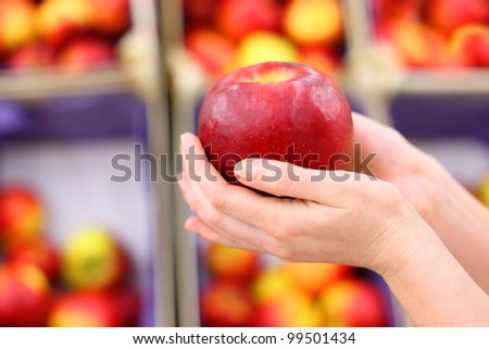 girl hands hold big red apple in shop; shallow depth of field - stock photo
