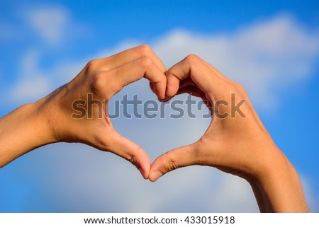 Girl hands in shape of love heart on blue sky with cloud.