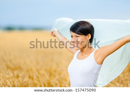 Girl hands silk scarf against rye field. Concept of freedom and happiness - stock photo